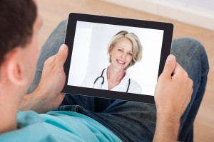 Man having video chat with female doctor on digital tablet at home